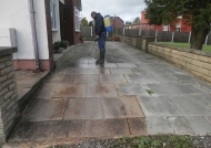 Applying chemical agents to clean driveway and kills weeds
